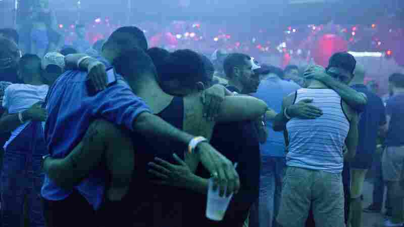 Club goers embrace at the approximate time one week ago that the Pulse nightclub mass shooting began. The music is turned off on the dance floor to observe a moment of silence at Parliament House, an LGBT nightclub early Sunday in Orlando, Fla.