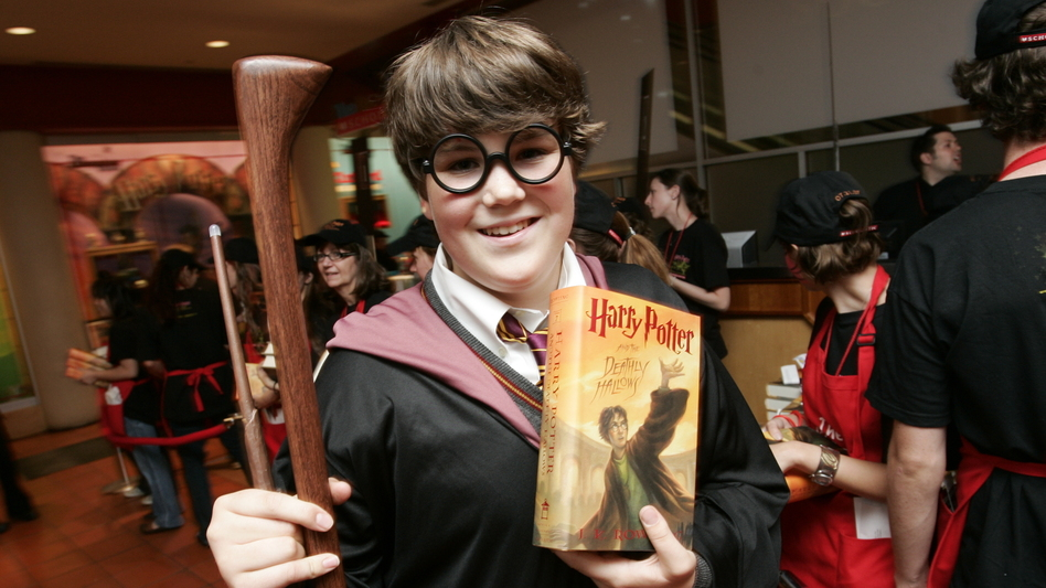 A fan holds a copy of <em>Harry Potter and the Deathly Hallows</em> at a book release party at Scholastic headquarters in New York in 2007. (Clark Jones/AP)