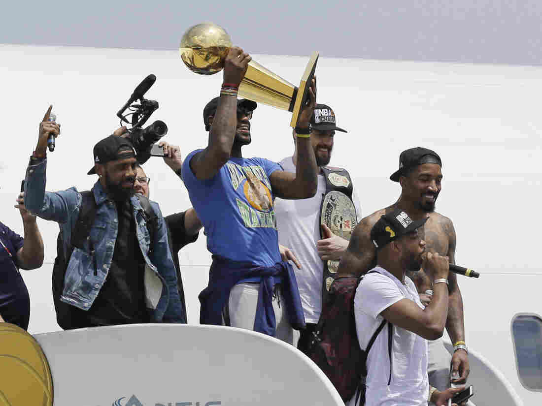 Cleveland Cavaliers' LeBron James holds up the NBA Championship trophy alongside teammates after arriving in Cleveland Monday.