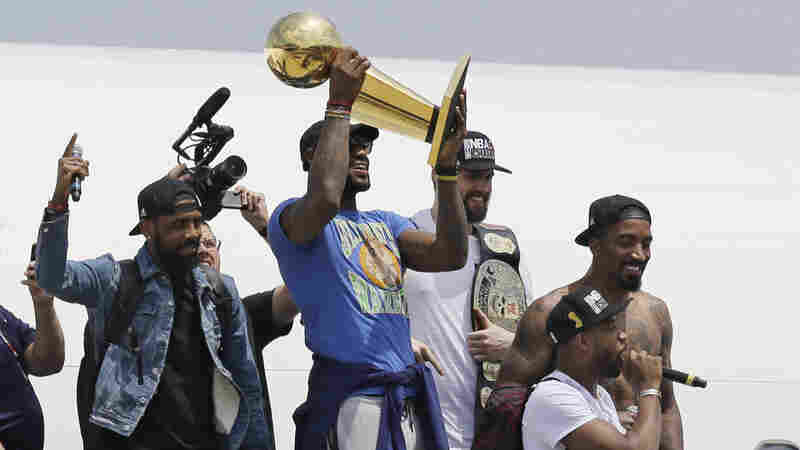 The Cleveland Cavaliers' LeBron James holds up the NBA championship trophy alongside teammates after arriving in Cleveland on Monday.