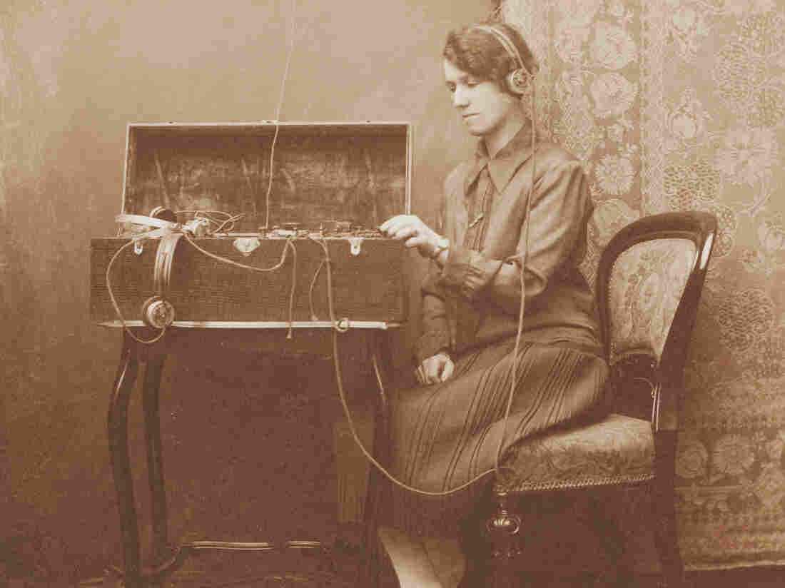 A woman uses a Morse code device housed within an oak box.