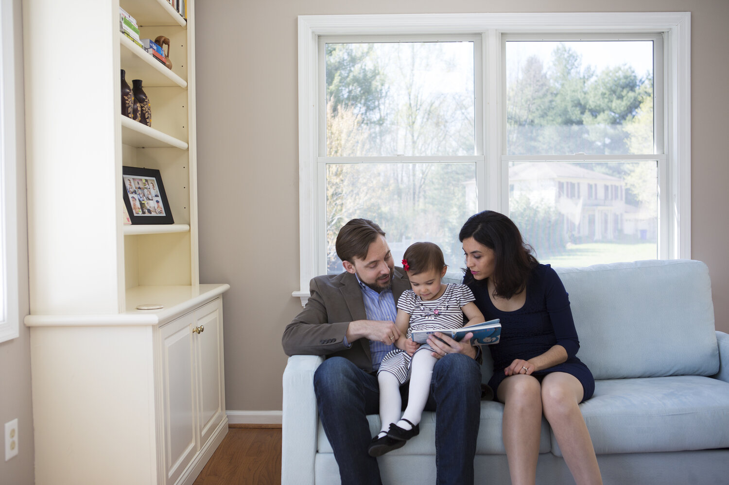 Travis and Sadiye Rieder read a book with their 2-year-old daughter, Sinem, in their Maryland home. Travis is a philosopher and ethicist who argues against having too many children, for moral and environmental reasons. His wife always wanted to have a big family.