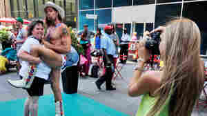 Robert Burck, The Naked Cowboy, poses for photos in one of Times Square's new color-coded designated activity zones in New York City. The new rules are aimed at controlling overly aggressive street performers. Violators face fines or jail time.