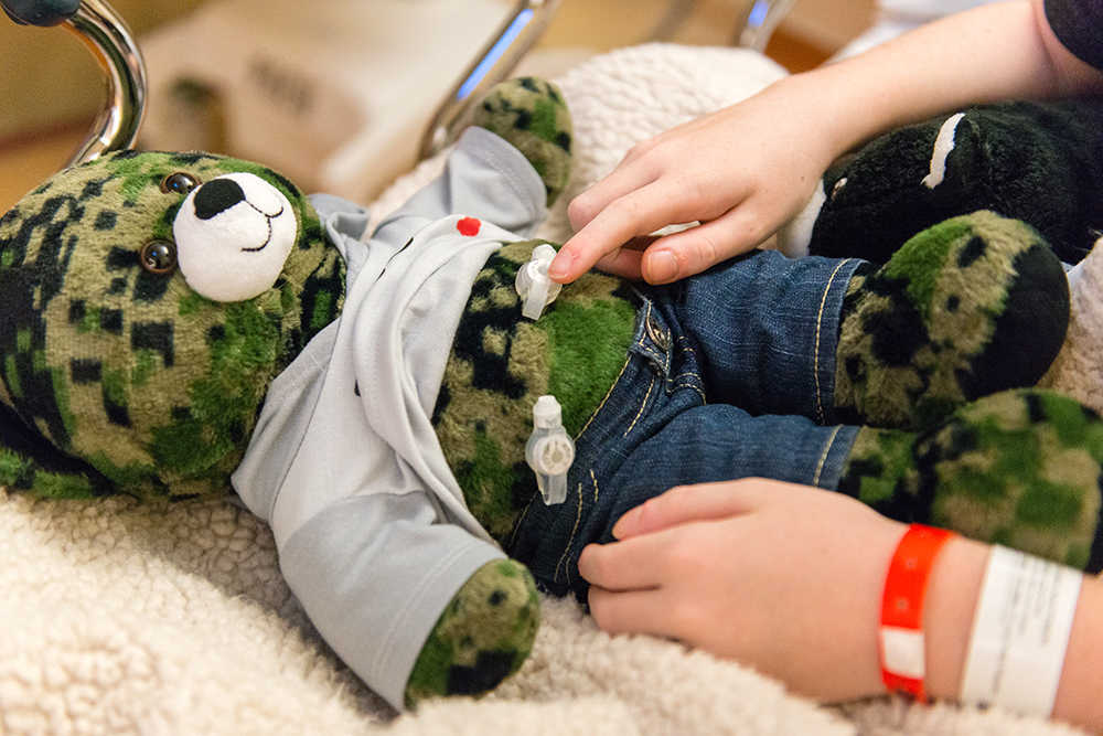Matthew Husby points to a gastrostomy tube on his teddy bear that is similar to the one surgeons inserted in his own stomach. Role-playing helps kids relax, doctors say.