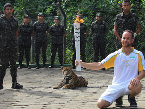 Brazilian physiotherapist Igor Simoes Andrade poses for a picture next to jaguar Juma as he takes part in the Olympic torch relay in Manaus, Brazil, on Monday.