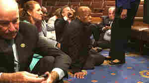 This photo provided by Rep. John Yarmuth, D-Ky., shows Democrat members of Congress, including Rep. John Lewis, D-Ga., (center) and Rep. Joe Courtney, D-Conn., (left) participating in a sit-down protest seeking a vote on gun control measures, Wednesday on the House floor.