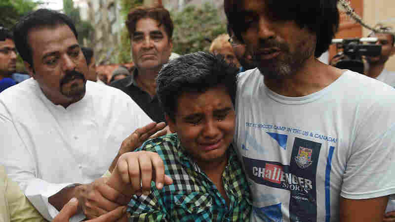 Relatives comfort Mujjudid Sabri (front, center), son of Pakistani singer Amjad Sabri, who was killed Wednesday in an attack by gunmen in Karachi.