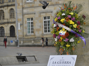 "A wreath placed before the statue of Simón Bolívar in Bogota's main square celebrates the peace accord between the Colombian government and the FARC leftist guerrilla group. The ribbon on the wreath says ""Farewell to War"" in Spanish; the sign beneath reads ""R.I.P. War in Colombia."""