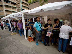 People line up outside the Venezuelan National Electoral Council in Caracas, the capital, on Monday. They were confirming their signatures supporting a recall referendum against President Nicolas Maduro. The country is suffering skyrocketing inflation and chronic shortages of basic goods.