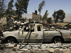 A pickup truck destroyed by a wildfire sits on a burned property near Lake Isabella, Calif. The wildfire that roared across dry brush and trees in the mountains of Central California gave residents little time to flee.