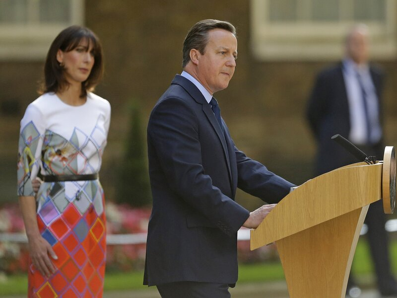Britain's Prime Minister David Cameron speaks outside 10 Downing St., London, as his wife, Samantha, looks on. Cameron says he will resign by the time of the Conservative Party conference in the fall.