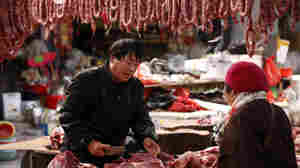 A vendor sells meat to a customer in a food market in Huaibei, Anhui, China, in February.