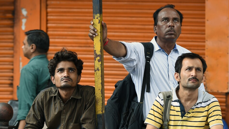 People watch stock prices on a digital broadcast outside the Bombay Stock Exchange on Friday. Currency, equity and oil markets around the world are feeling the effects of the British vote to leave the EU. (AFP/Getty Images)