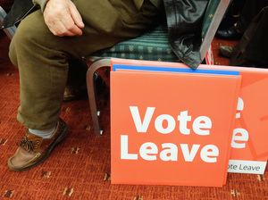 A man sits next to campaign posters in Newcastle upon Tyne, England, in April. On June 23, the United Kingdom voted to leave the European Union. What comes next? (Photo by Ian Forsyth/Getty Images)