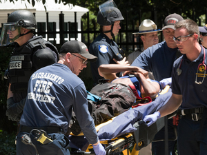 Paramedics rush a stabbing victim away on a gurney on Sunday, after clashes outside the California Capitol between white nationalist demonstrators and counter-protesters.