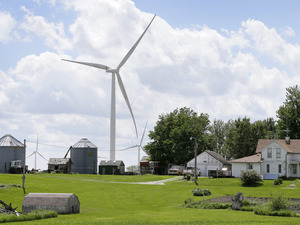 A wind turbine stands over a farm house in Adair, Iowa.