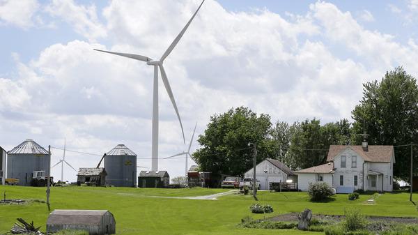 A wind turbine stands over a farmhouse in Adair, Iowa.