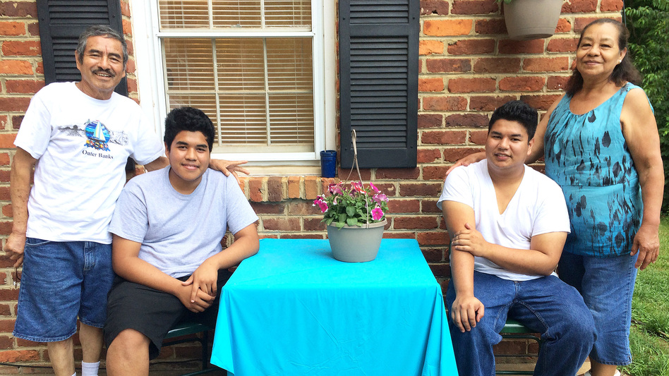Edson Escobar, 16, (seated, left) and his brother Alex Escobar, 18, (right), with their grandparents Ricardo and Sara Tejada in central Virginia. Edson and Alex came to the U.S. from El Salvador separately two years apart to escape their abusive father. (NPR)