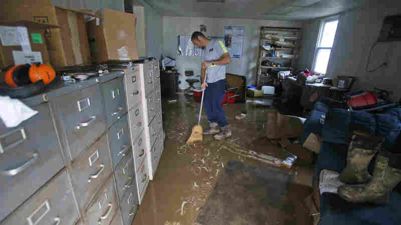 Shane Altzier sweeps out the mud from the utilities office in Rainelle, W.Va., one of the towns hardest hit by floods that tore through the state on Friday. More rain this week has slowed cleanup efforts.