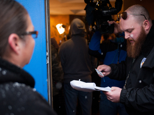 Kurt Britz checks a driver's license at the 3-D Denver Discrete Dispensary on January 1, 2014, the first day recreational marijuana sales were legal in Colorado. Possession remains illegal for those under 21 years old, and statistics show a widening racial gap in arrests for those offenses.