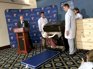 Elliot Kaye (left), chairman of the Consumer Product Safety Commission, and CPSC employees watch as an IKEA Malm model chest of drawers falls on a 28-pound dummy during a live demonstration Tuesday at the National Press Club in Washington, D.C.