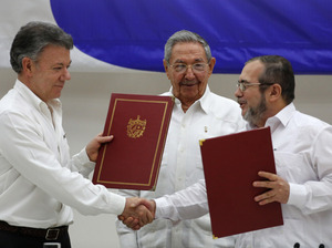"Colombian President Juan Manuel Santos (left) and FARC commander Timoleon Jimenez (right) shake hands as Raul Castro looks on at a signing ceremony of a cease-fire deal in Havana last Thursday. ""It is the first time ever that a guerrilla group lays down its arms to submit to a justice system where they are going to be investigated, judged, and condemned and sanctioned,"" Santos told NPR."