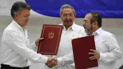 "Colombian President Juan Manuel Santos, left, and FARC commander Timoleon Jimenez, right, shake hands as Raul Castro looks on at a signing ceremony of a ceasefire deal in Havana last Thursday. ""It is the first time ever that a guerrilla group lays down its arms to submit to a justice system where they are going to be investigated, judged, and condemned and sanctioned,"" Santos told NPR."