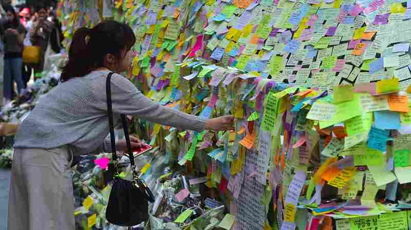 South Koreans leave notes at an exit of Gangnam subway station in Seoul. It was turned into a makeshift memorial for a 23-year-old woman who was stabbed to death by a male stranger.