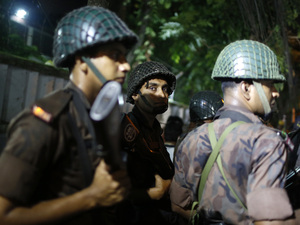 Bangladeshi security personnel stand guard near a cafe that reportedly has been attacked by unidentified gunmen Friday in the capital city, Dhaka.