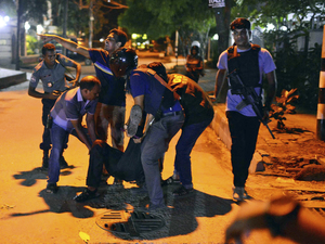 People help an unidentified injured person after gunmen attacked a cafe popular with foreigners in Bangladesh's capital, Dhaka, on Friday.