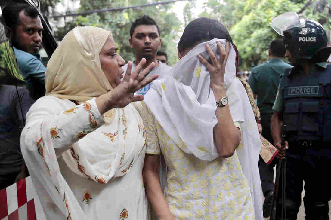A relative tries to console Semin Rahman (covering face), whose son is missing after militants took hostages in a restaurant popular with foreigners in Dhaka, Bangladesh.