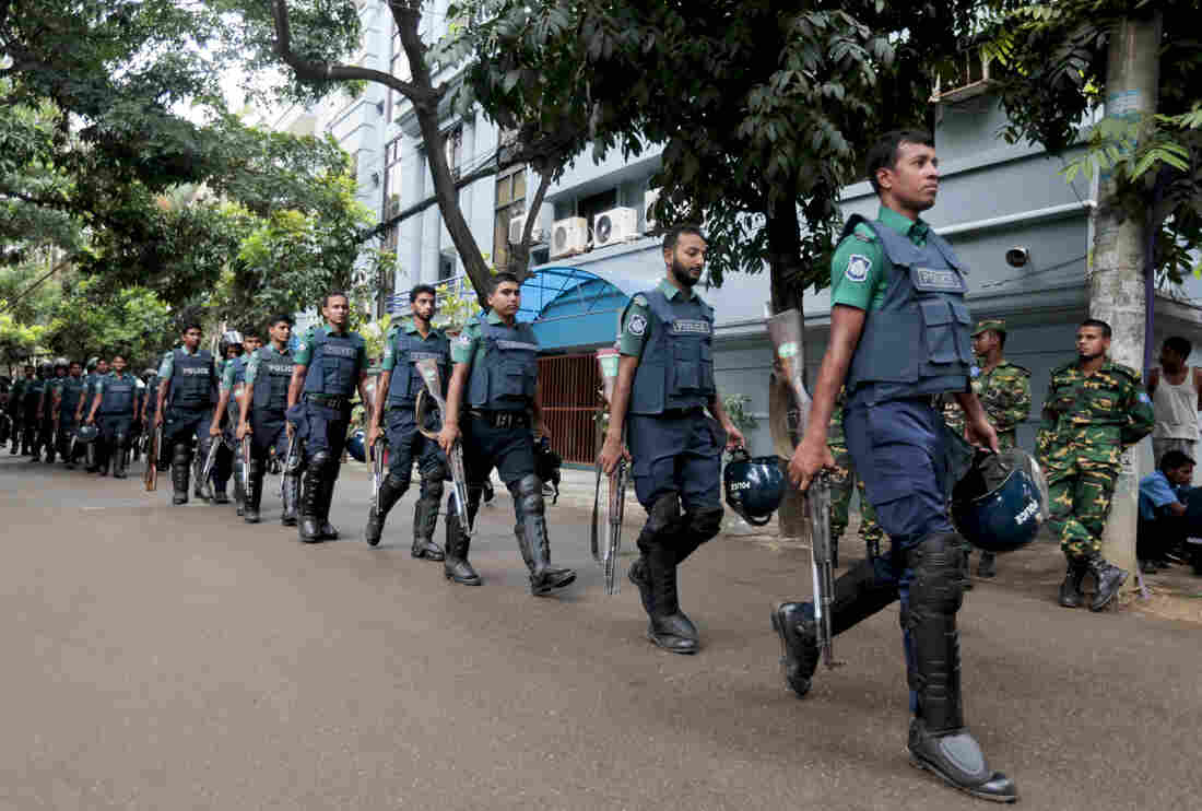 Bangladeshi policemen patrol the area around the site of the attack in Dhaka, Bangladesh, on Saturday.