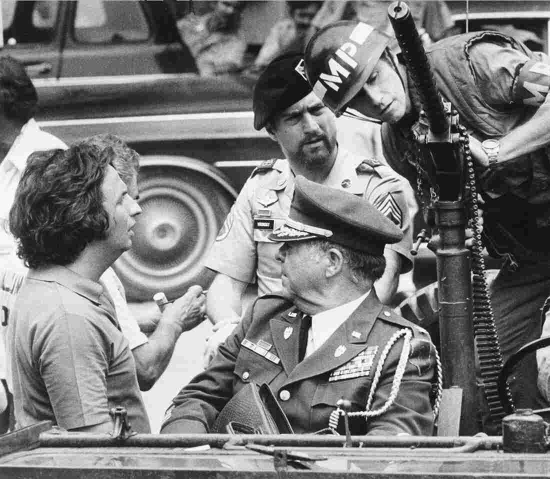 "Director Michael Cimino (left) talks with actor Robert De Niro (center wearing beret) during a break while filming ""The Deer Hunter"" on location in Bangkok."