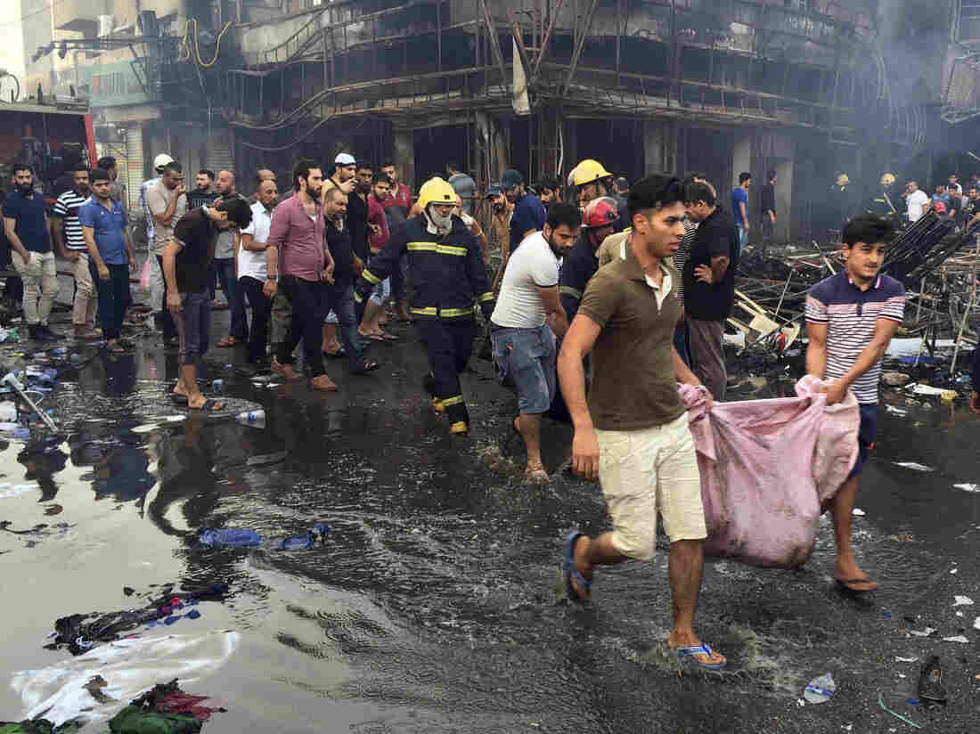 Iraqi firefighters and civilians evacuate bodies of victims killed from a bomb at a commercial area on Sunday in Karada neighborhood, Baghdad, Iraq.