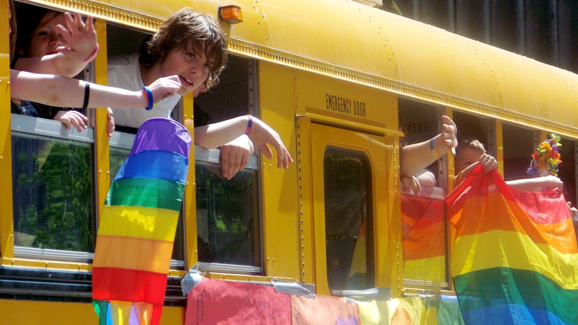 LGBTQ students on a school bus waving a rainbow flag