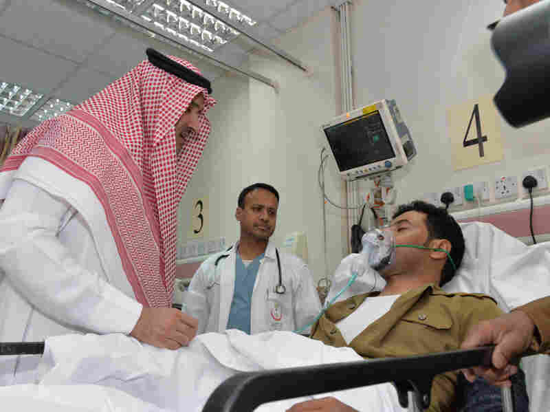 Saudi Prince Faisal bin Salman bin Abdulaziz (left) visits an injured policeman at a local hospital following a suicide attack near the security headquarters of the Prophet's Mosque in Medina on July 4.
