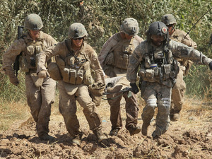 U.S. troops carry a wounded Afghani man to a MEDEVAC helicopter.