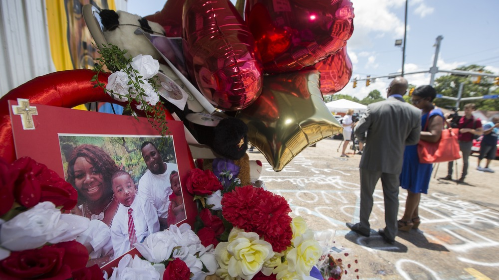 A photo of Alton Sterling and his family is displayed at a memorial outside the Triple S Mart on Thursday in Baton Rouge, La. Sterling was shot by a police officer in front of the convenience store on Tuesday.
