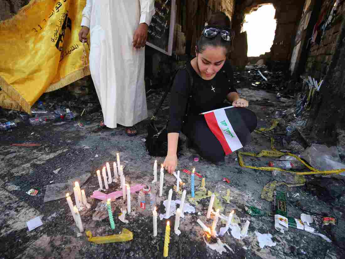 An Iraqi woman mourns at the site of a July 3rd attack, claimed by Islamic State, which killed at least 292 people. Baghdad's security chief has since been fired, but outrage at the government still remains high.