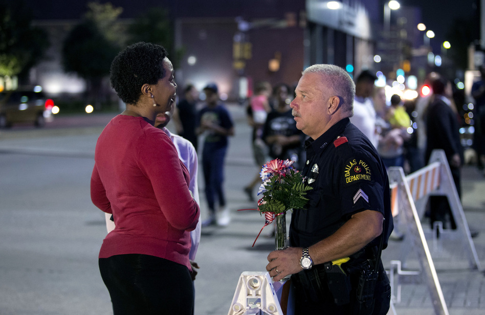 A woman speaks with an officer at a vigil outside Dallas police headquarters in Dallas on Friday. (Bilgin Sasmaz/Anadolu Agency via Getty Images)