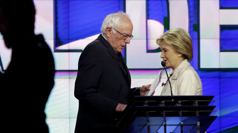 Bernie Sanders and Hillary Clinton pass during a break at a Democratic debate April 14 in New York.