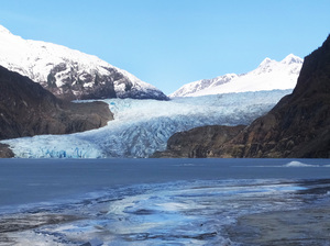 Light shines on the mountains behind the Mendenhall Glacier in Juneau, Alaska. Guides are using the glacier's rapid retreat as a stark lesson on the effects of climate change.