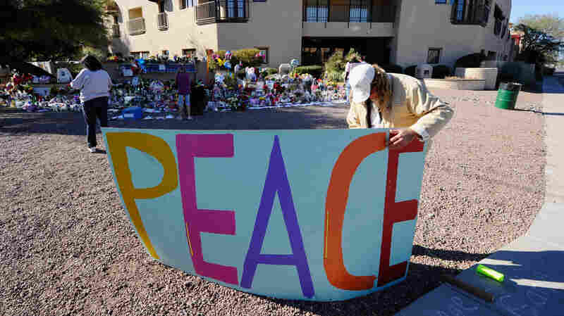 Troy Wine places a large peace sign at a makeshift memorial outside the office of Rep. Gabrielle Giffords in Tucson, Ariz.
