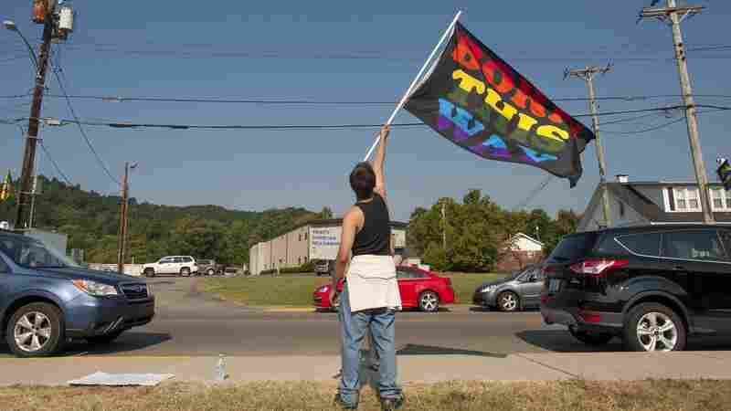 "A same-sex marriage supporter waves a flag reading ""Born This Way: along West Main Street in Morehead, Ky."