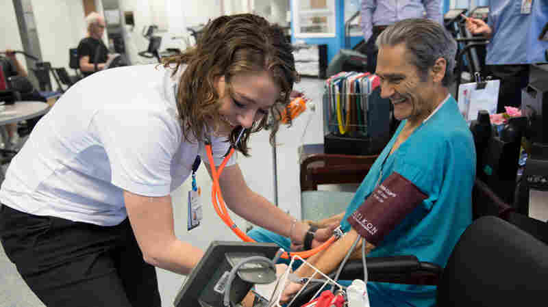 Exercise physiologist Courtney Conners checks Mario Oikonomides' vital signs before his cardiac rehab workout at the University of Virginia Health System clinic.