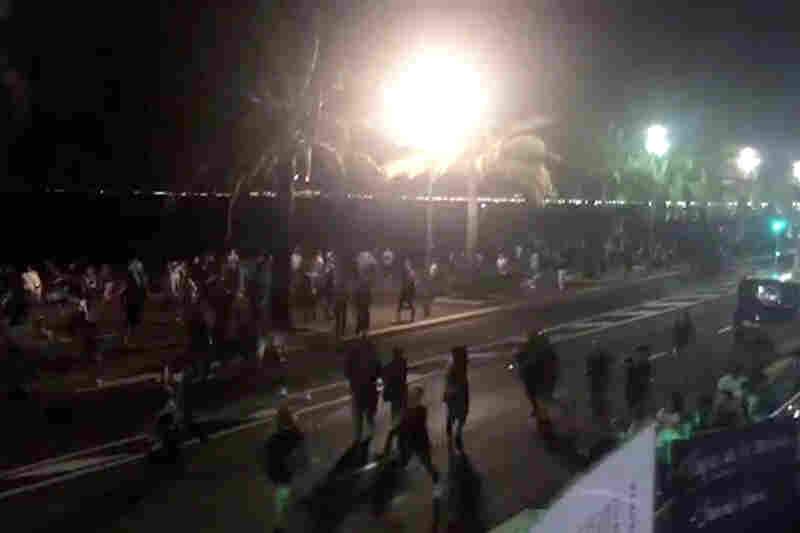 In this video screenshot, people run from the scene after a truck drove onto the sidewalk and hit a crowd of revelers Thursday.