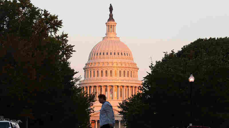 A pedestrian crosses a road with the U.S. Capitol building in the background on August 1.
