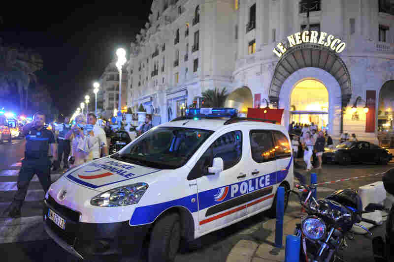 A police car is parked near the scene of an attack after a truck plowed through a crowd of revelers who had gathered to watch fireworks in Nice.