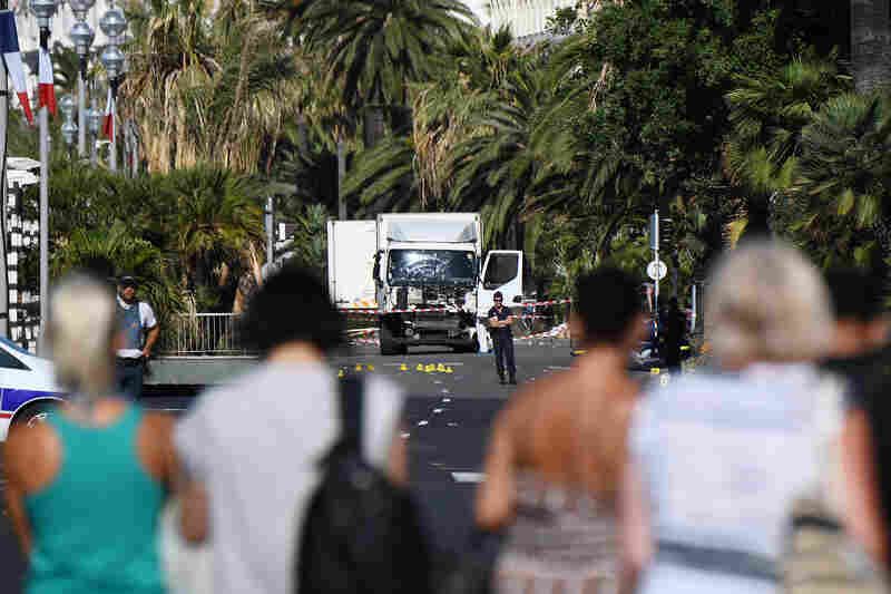 People look at a truck guarded by the police on the Promenade des Anglais seafront in Nice, France, on Friday, hours after it drove into a crowd watching a fireworks display. More than 80 people were killed as a truck drove through crowds celebrating Bastille Day.