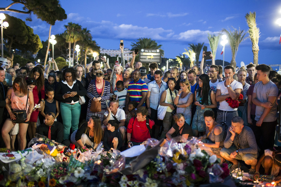 People gather at a makeshift memorial to honor the victims of an attack on Friday, near the area where a truck mowed through revelers in Nice, France. (Laurent Cipriani/AP)